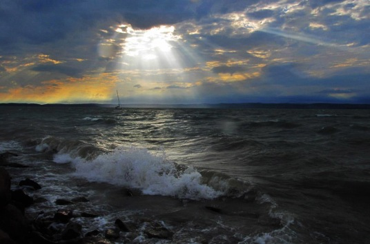 sun shining through clouds on the water
